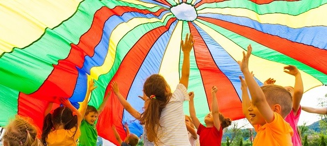 joyous-classmates-jumping-under-colorful-parachute-in-the-summer-outdoors
