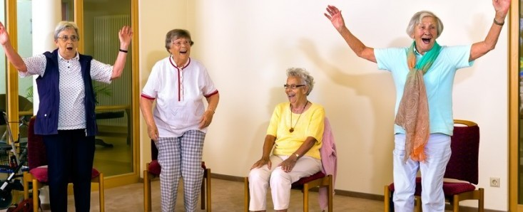 Group of four cheering senior women practicing light aerobic exercises with chairs for fitness class indoors.